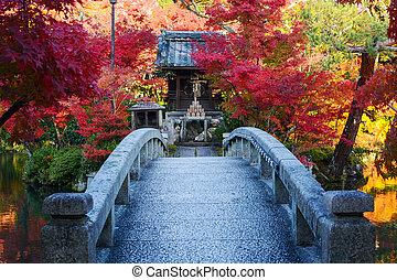Bridge to a pond island with a prayer shrine and red fall maple trees