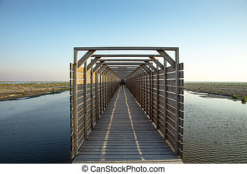Bridge to bird watching hut on the Markerwadden. Wooden canopy on a jetty that leads to the entrance of a birdwatch view on artificial islands in the Markermeer.