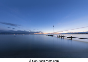 BRIDGE TO THE LAKE IN BLUE HOUR, PHOTO OF A BLUE LAKE WITH BRIDGE AT SUNSET WITH COPY SPACE