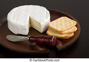 Brie and butter cracker on a wooden cheese plate with cheese knife