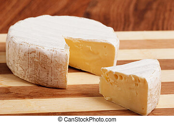 A head of brie cheese with one section cut