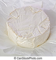 A small wheel of brie cheese on wrapping paper.