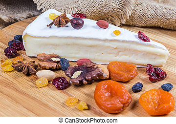 Brie cheese among nuts, dried fruits, closeup in selective focus