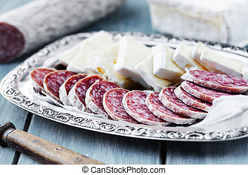 Pieces of brie cheese and air dried salami on a tray