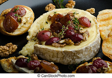 Brie cheese baked with nuts and grapes, tasty and crispy...