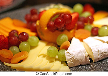 Brie Swiss and Fruit - A deli tray of different cheeses and...