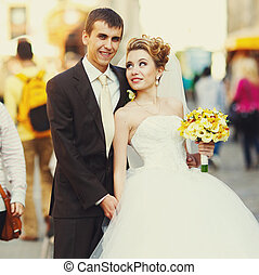 Bried looks at a groom with love posing on the street