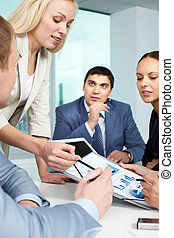 Briefing - Businesswoman showing charts to colleagues