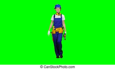 Brigadier girl comes with a drill in her hands. Green screen. Side view