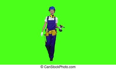 Brigadier girl comes with a drill in her hands. Green screen. Slow motion