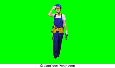 Brigadier girl in glasses comes with a drill in her hands. Green screen