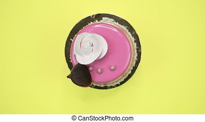 Bright and colorful cake close-up on a yellow background. Rotating Top view.