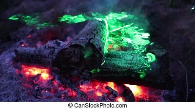 bright and fervent fire at night with a green laser light