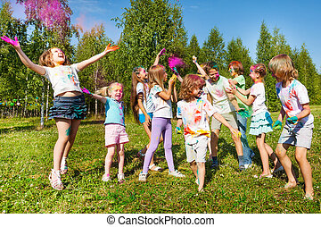 Bright and happy kids playing with colored powder