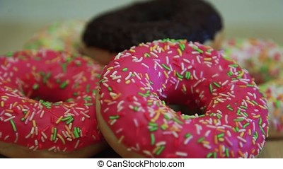 Bright appetizing donuts on a wooden table. Close-up. HD