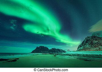 Bright aurora, sea, sandy beach and snowy mountains