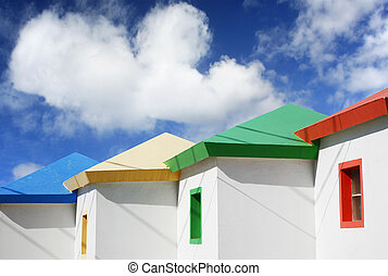 Bright beach huts with dramatic blue sky