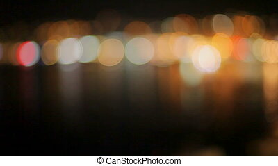 Bright beautiful colorful bokeh on a dark background. Reflection of lights in dark water