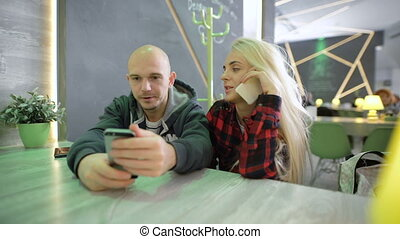 Bright blonde girl with long hair in a checkered red shirt tired of talking on the phone with a friend, and sit in a cafe near the qute bald man in a green jacket with a hood,