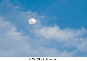 Bright blue sky with clouds and the day time moon.
