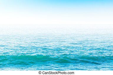 Rippled water surface in bright blue colors with blured horizon line