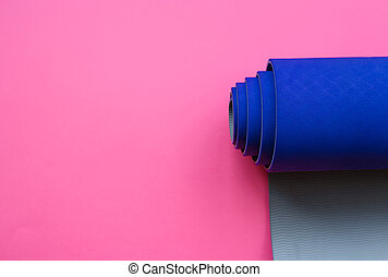 Bright blue yoga mat on a pink background