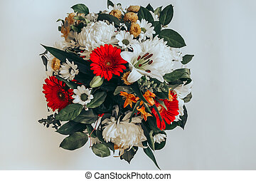 Bright bouquet of gerberas, chrysanthemums, lilies, green leaves on a light background. Top view. Selective focus.