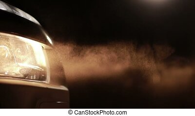 Bright car headlights in clouds of dust at night - Yellow...