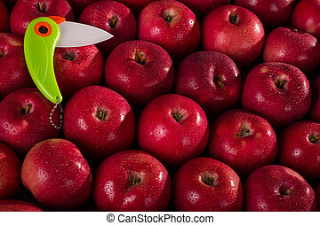 Bright ceramic knife on the background of fresh juicy apples in drops