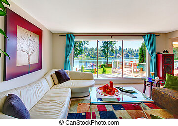 Bright classic living room interior with white leather couch and beautiful water view.