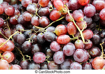 Bright clusters of ripe grapes are sold in the market