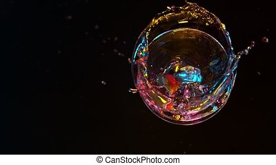 Bright cocktail with falling ice cube on dark background.