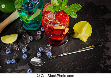 Bright cocktails with mint, lime, ice, berries and carambola on the black background. Refreshing summer beverages. Copy space.