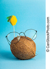 Bright coconut in the shape of a face on a blue summer concept