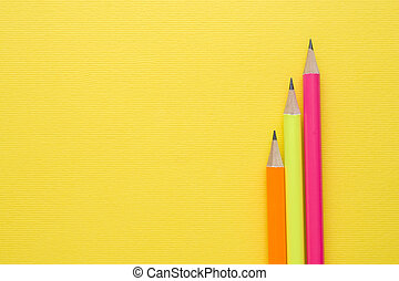 Bright colored pencils on yellow background. Copy space