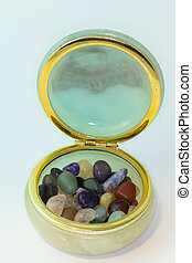 Bright colorful natural stones in jewelry box on a white background