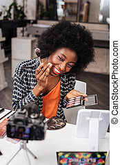 Pretty dark-skinned woman with coral lipstick doing makeup