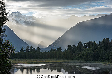 Bright contrast rays of morning sun over the Lake Matheson