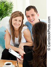Bright couple concluding a car contract with a female dealer