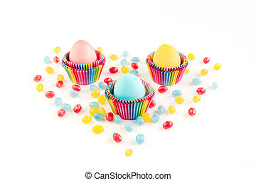 Bright creative Easter decoration of colorful eggs in raibow colored paper forms for cupcakes on white background decorated with jelly candies. Place for text.