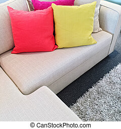 Bright cushions on gray corner sofa