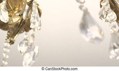 Bright details of a chandelier on a white background. Slowly