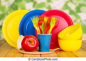 Bright disposable plates, cups, plastic bowls, forks on ...