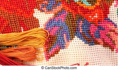 Bright embroidery with flowers and floss, close up -...