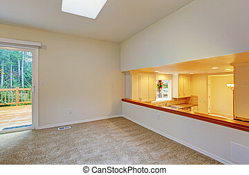 Bright empty room with walkout deck and kitchen view