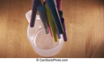 bright felt-tip pens fall in a glass, slow motion
