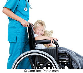 Bright female doctor carrying adorable little boy with his teddy bear in the wheelchair at the hospital