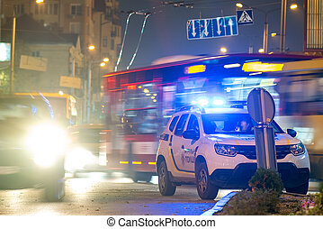 Bright flashing blue lights of police patrol car parked on city street with night traffic.
