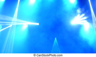 Bright flashing concert spotlights lasers and smoke at the...