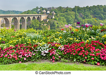 Bright Flowerbed and tall stone bridge as a background